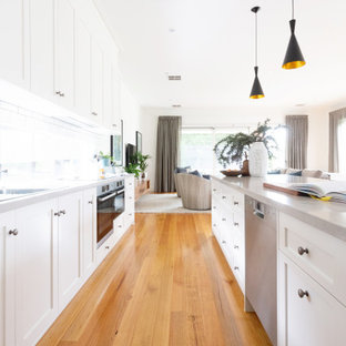 Design ideas for a large transitional galley kitchen in Melbourne with an undermount sink, shaker cabinets, white cabinets, window splashback, stainless steel appliances, multiple islands, brown floor and grey benchtop.