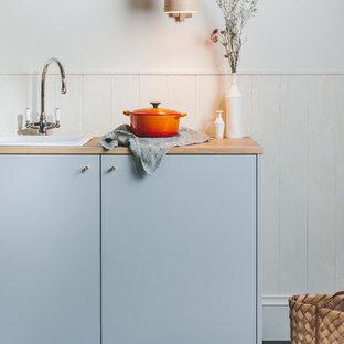 Idee per una piccola cucina nordica con lavello a vasca singola, ante lisce, ante grigie, top in legno, paraspruzzi bianco, paraspruzzi in legno, elettrodomestici da incasso, pavimento in legno verniciato, nessuna isola, pavimento nero e top marrone