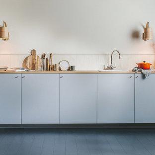 Nordisk inredning av ett litet brun linjärt brunt kök med öppen planlösning, med en enkel diskho, släta luckor, grå skåp, träbänkskiva, vitt stänkskydd, stänkskydd i trä, integrerade vitvaror, målat trägolv och svart golv
