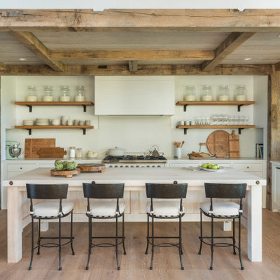 Country u-shaped medium tone wood floor and brown floor kitchen photo in Boston with a farmhouse sink, shaker cabinets, white cabinets, white backsplash, stone slab backsplash, paneled appliances, an island and white countertops