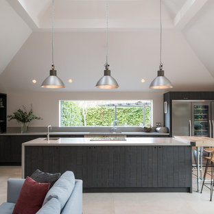 Large country open plan kitchen in Other with dark wood cabinets, composite countertops, stainless steel appliances, limestone flooring, a double-bowl sink, flat-panel cabinets, window splashback, beige floors, grey worktops and multiple islands.