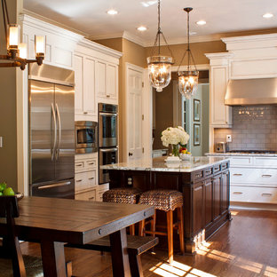 Example of a classic l-shaped eat-in kitchen design in Atlanta with granite countertops, recessed-panel cabinets, white cabinets, multicolored backsplash, glass tile backsplash and stainless steel appliances