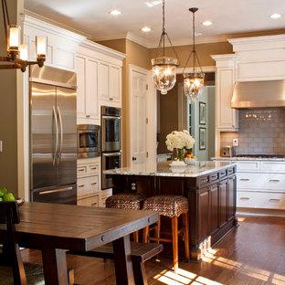Inspiration pour une cuisine américaine traditionnelle en L avec un plan de travail en granite, un placard avec porte à panneau encastré, des portes de placard blanches, une crédence multicolore, une crédence en carreau de verre et un électroménager en acier inoxydable.