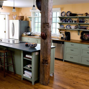 This is an example of a country galley kitchen in Boston with stainless steel appliances, open cabinets, green cabinets and wood benchtops.