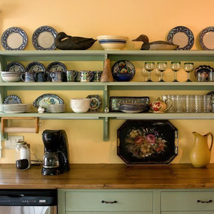 Country kitchen in Boston with wood benchtops, open cabinets and green cabinets.