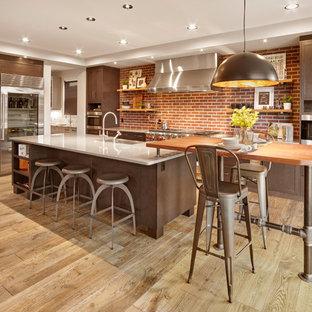 エドモントンのインダストリアルスタイルのおしゃれなキッチン (エプロンフロントシンク、シェーカースタイル扉のキャビネット、濃色木目調キャビネット、赤いキッチンパネル、レンガのキッチンパネル、シルバーの調理設備の、無垢フローリング、茶色い床、白いキッチンカウンター) の写真