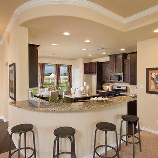 Ispirazione per una cucina di medie dimensioni con ante con riquadro incassato, ante in legno bruno, top in granito, paraspruzzi beige, paraspruzzi in gres porcellanato, elettrodomestici in acciaio inossidabile, parquet scuro, isola, pavimento marrone e top giallo