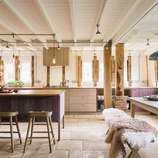 Cette photo montre une grand cuisine ouverte linéaire montagne avec un placard à porte plane, des portes de placard en bois clair, un plan de travail en bois et un îlot central.