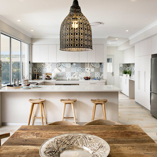 This is an example of a large coastal u-shaped kitchen pantry in Perth with a submerged sink, flat-panel cabinets, light wood cabinets, engineered stone countertops, multi-coloured splashback, ceramic splashback, stainless steel appliances, ceramic flooring and no island.