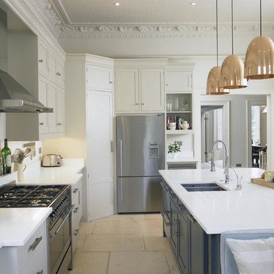Example of a large transitional kitchen design in London with shaker cabinets, white cabinets, quartz countertops, white backsplash, an island, a double-bowl sink and stainless steel appliances