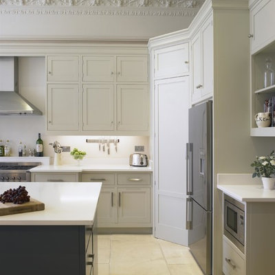 Large transitional kitchen photo in London with shaker cabinets, white cabinets, quartz countertops, white backsplash, an island and stainless steel appliances