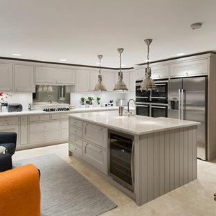 Design ideas for a large modern u-shaped kitchen/diner in Surrey with a belfast sink, beige cabinets, marble worktops, white splashback, marble splashback, integrated appliances, porcelain flooring, an island, beige floors and white worktops.