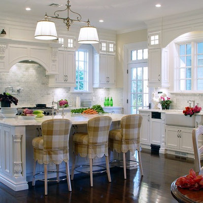 Large elegant u-shaped dark wood floor and brown floor eat-in kitchen photo in New York with a farmhouse sink, flat-panel cabinets, white cabinets, marble countertops, white backsplash, subway tile backsplash, stainless steel appliances and an island