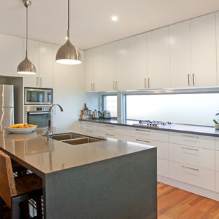 Photo of a contemporary u-shaped kitchen in Central Coast with an undermount sink, flat-panel cabinets, white cabinets, window splashback, stainless steel appliances, medium hardwood floors, with island, brown floor and grey benchtop.