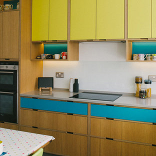Design ideas for a medium sized retro u-shaped kitchen/diner in Other with a built-in sink, flat-panel cabinets, yellow cabinets, quartz worktops, yellow splashback, glass tiled splashback, stainless steel appliances, concrete flooring and no island.