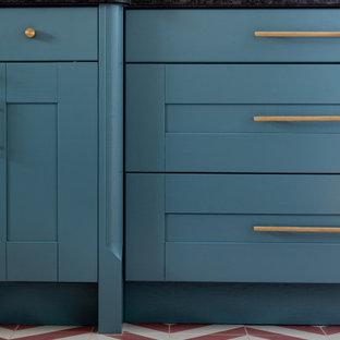 ハートフォードシャーのコンテンポラリースタイルのおしゃれなキッチン (ドロップインシンク、シェーカースタイル扉のキャビネット、青いキャビネット、御影石カウンター、青いキッチンパネル、ガラス板のキッチンパネル、シルバーの調理設備、セメントタイルの床、赤い床、黒いキッチンカウンター) の写真