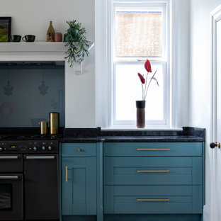 Design ideas for a contemporary kitchen in Hertfordshire with a built-in sink, shaker cabinets, blue cabinets, granite worktops, blue splashback, glass sheet splashback, stainless steel appliances, cement flooring, red floors and black worktops.