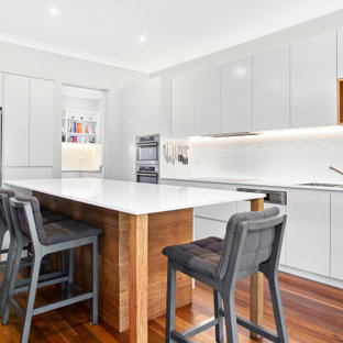 Large contemporary l-shaped kitchen in Sydney with an undermount sink, flat-panel cabinets, white cabinets, white splashback, with island, brown floor and white benchtop.
