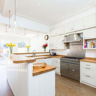 ハンプシャーの広いエクレクティックスタイルのおしゃれなキッチン (シングルシンク、シェーカースタイル扉のキャビネット、白いキャビネット、木材カウンター、シルバーの調理設備、淡色無垢フローリング、アイランドなし) の写真