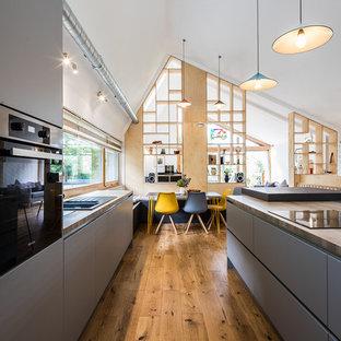 Inredning av ett modernt stort brun brunt kök, med en dubbel diskho, grå skåp, träbänkskiva, fönster som stänkskydd, mellanmörkt trägolv, en köksö och brunt golv