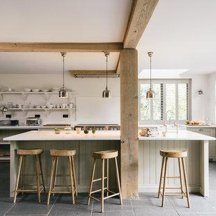 Lantlig inredning av ett stort linjärt kök, med en rustik diskho, skåp i shakerstil, grå skåp, bänkskiva i kvartsit, vitt stänkskydd och en köksö