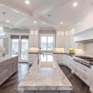 Large transitional open concept kitchen inspiration - Example of a large transitional u-shaped medium tone wood floor and brown floor open concept kitchen design in Salt Lake City with an undermount sink, recessed-panel cabinets, white cabinets, marble countertops, white backsplash, subway tile backsplash, stainless steel appliances and two islands