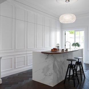 Пример оригинального дизайна интерьера: параллельная кухня - столовая среднего размера в викторианском стиле с врезной раковиной, белыми фасадами, мраморной столешницей, белым фартуком, фартуком из каменной плиты, белой техникой, темным паркетным полом и островом