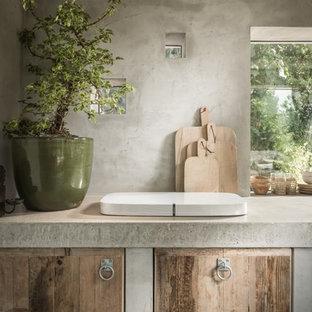 Inspiration för ett litet rustikt beige linjärt beige kök med öppen planlösning, med släta luckor, skåp i mellenmörkt trä, bänkskiva i betong, integrerade vitvaror, betonggolv och beiget golv