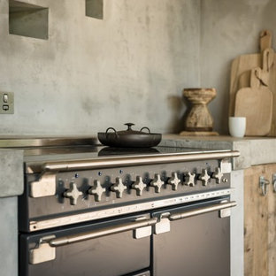 コーンウォールの小さいラスティックスタイルのおしゃれなキッチン (フラットパネル扉のキャビネット、中間色木目調キャビネット、コンクリートカウンター、黒い調理設備、コンクリートの床、アイランドなし、ベージュの床、ベージュのキッチンカウンター) の写真