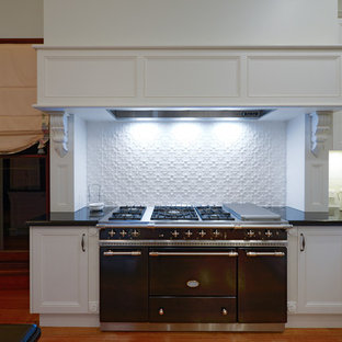 Inspiration for an expansive victorian u-shaped kitchen/diner in Newcastle - Maitland with a belfast sink, recessed-panel cabinets, white cabinets, granite worktops, white splashback, metro tiled splashback, medium hardwood flooring and an island.