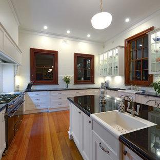 ニューカッスルの巨大なヴィクトリアン調のおしゃれなキッチン (エプロンフロントシンク、落し込みパネル扉のキャビネット、白いキャビネット、御影石カウンター、白いキッチンパネル、サブウェイタイルのキッチンパネル、無垢フローリング) の写真