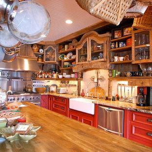 Inredning av ett lantligt stort kök, med en rustik diskho, röda skåp, bänkskiva i betong, vitt stänkskydd, stänkskydd i stenkakel, rostfria vitvaror, en köksö och luckor med infälld panel