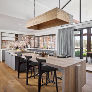 Contemporary l-shaped kitchen in Perth with flat-panel cabinets, grey cabinets, red splashback, brick splashback, medium hardwood floors, with island, brown floor and grey benchtop.
