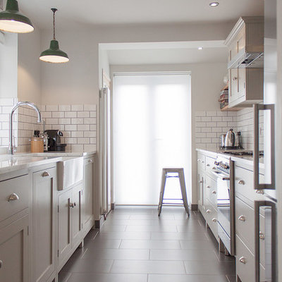 Enclosed kitchen - mid-sized contemporary galley enclosed kitchen idea in London with a farmhouse sink, shaker cabinets, white backsplash and subway tile backsplash