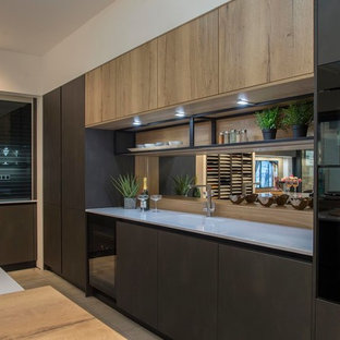 Design ideas for a large contemporary galley eat-in kitchen in Other with an integrated sink, flat-panel cabinets, grey cabinets, quartzite benchtops, metallic splashback, mirror splashback, black appliances, ceramic floors, with island, beige floor and white benchtop.