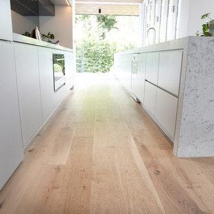Immagine di una cucina scandinava di medie dimensioni con lavello sottopiano, ante lisce, ante bianche, top in granito, paraspruzzi nero, paraspruzzi con lastra di vetro, elettrodomestici bianchi e parquet chiaro
