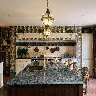 Foto di una cucina tradizionale di medie dimensioni con lavello sottopiano, ante con riquadro incassato, ante beige, top in granito, parquet scuro, isola, pavimento blu e top grigio