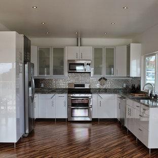 Geschlossene, Mittelgroße Moderne Küche ohne Insel in U-Form mit Unterbauwaschbecken, Glasfronten, weißen Schränken, Granit-Arbeitsplatte, Küchenrückwand in Metallic, Rückwand aus Keramikfliesen, Küchengeräten aus Edelstahl und Bambusparkett in San Diego