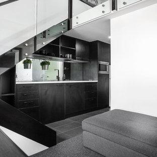 Ejemplo de cocina comedor lineal, minimalista, pequeña, sin isla, con fregadero encastrado, armarios con paneles lisos, puertas de armario negras, encimera de granito, salpicadero con efecto espejo, electrodomésticos de acero inoxidable y moqueta