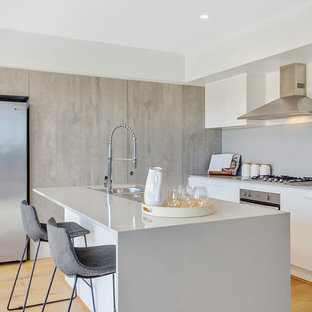Inspiration for a contemporary l-shaped kitchen in Brisbane with a drop-in sink, flat-panel cabinets, white cabinets, grey splashback, stainless steel appliances, light hardwood floors, with island, beige floor and white benchtop.