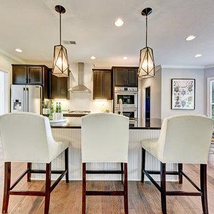 Klassische Wohnküche in L-Form mit Schrankfronten mit vertiefter Füllung, braunen Schränken, Küchenrückwand in Weiß, Küchengeräten aus Edelstahl, braunem Holzboden, Kücheninsel, braunem Boden und schwarzer Arbeitsplatte in Sonstige