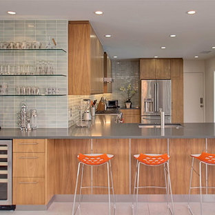 Inspiration for a midcentury l-shaped eat-in kitchen in Los Angeles with flat-panel cabinets, medium wood cabinets, grey splashback, subway tile splashback, stainless steel appliances, concrete floors and a peninsula.