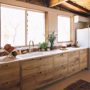 サンタフェスタイルのおしゃれなキッチン (マルチカラーのキッチンパネル、セラミックタイルのキッチンパネル、フラットパネル扉のキャビネット、中間色木目調キャビネット、白い調理設備、ベージュの床) の写真