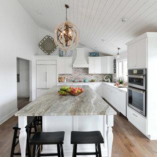 Inspiration för stora klassiska grått kök, med en undermonterad diskho, luckor med infälld panel, vita skåp, granitbänkskiva, grått stänkskydd, stänkskydd i tegel, integrerade vitvaror, mellanmörkt trägolv, en köksö och brunt golv