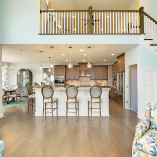 Photo of a large beach style eat-in kitchen in Other with louvered cabinets, brown cabinets, quartz benchtops, beige splashback, mosaic tile splashback, stainless steel appliances, medium hardwood floors, multiple islands and brown floor.