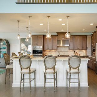 Design ideas for a large beach style eat-in kitchen in Other with louvered cabinets, brown cabinets, quartz benchtops, beige splashback, mosaic tile splashback, stainless steel appliances, medium hardwood floors, multiple islands and brown floor.