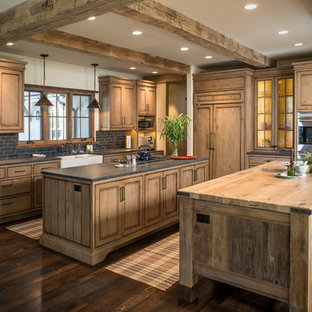 Rustic kitchen inspiration - Inspiration for a rustic dark wood floor kitchen remodel in Other with wood countertops, two islands, recessed-panel cabinets, medium tone wood cabinets and paneled appliances