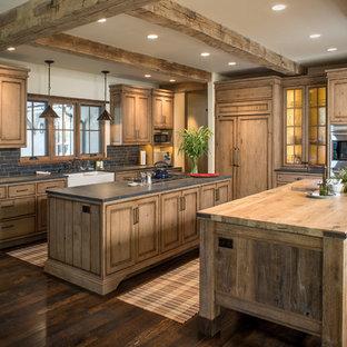 Ejemplo de cocina rústica con encimera de madera, suelo de madera oscura, dos o más islas, armarios con paneles empotrados, puertas de armario de madera oscura y electrodomésticos con paneles