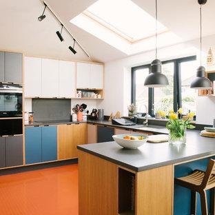 Foto di una cucina design di medie dimensioni con ante lisce, paraspruzzi grigio, penisola, pavimento arancione, top grigio, lavello sottopiano, ante blu e elettrodomestici neri