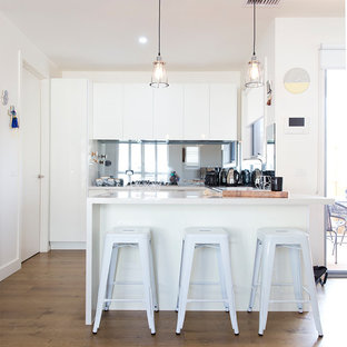 This is an example of a contemporary u-shaped kitchen in Melbourne with flat-panel cabinets, white cabinets, mirror splashback, dark hardwood floors, a peninsula and brown floor.